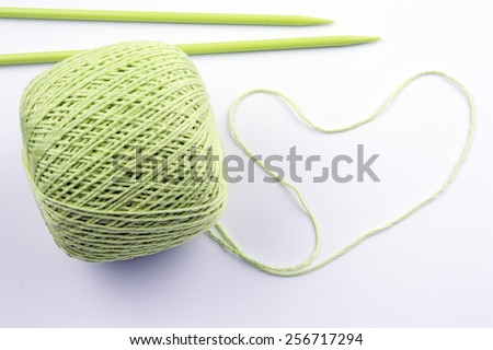 wool ball of yarn in heart form on white background - stock photo