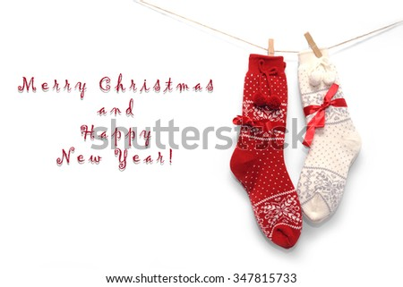Wool Christmas socks, red and white, hanging on white