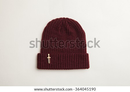 Wool hat on the white background with wooden brooch - stock photo