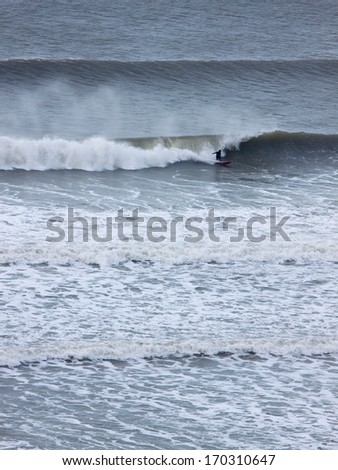 WOOLACOMBE BAY, UK - December 11, 2013: Winter surfing off the North Devon coast. This stretch of coastline has long been popular with surfers in England