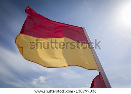 WOOLACOMBE, UK - MAY 19: A red and yellow safety flag fluttering in the wind against a bright blue sky at Woolacombe on 19th May 2011. The flag is used by lifeguards to mark the safe swimming area.