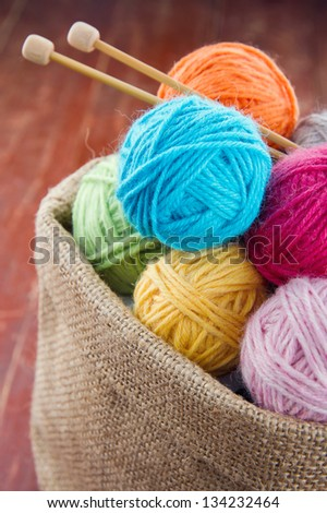 Woolen balls of yarn and wooden knitting needles in a rustic craft bag on red old wooden background - stock photo