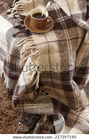 Woolen checked plaid, slippers and coffee cup on shaggy carpet. - stock photo
