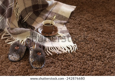 Woolen checked plaid, slippers and coffee cup on shaggy carpet. Focus on slippers.