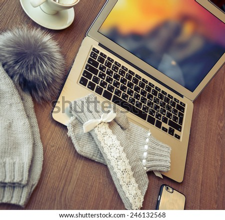 Woolen hat with pompon and mitten near a laptop and cup if coffee on the wooden table - stock photo
