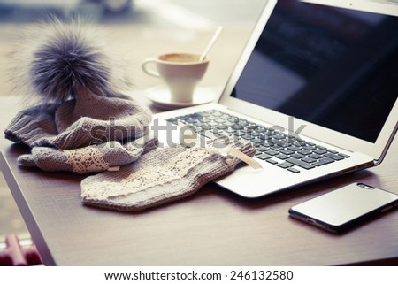 Woolen hat with pompon and mitten near a laptop and cup of coffe on the wooden table - stock photo
