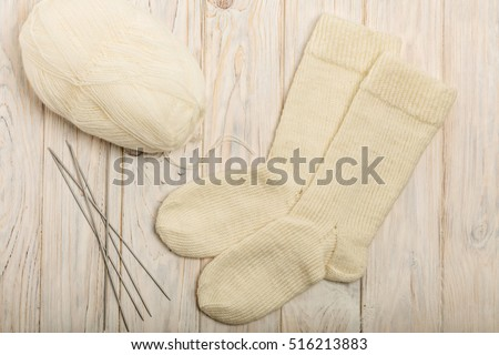 Woolen knitted white socks on a light wooden background.