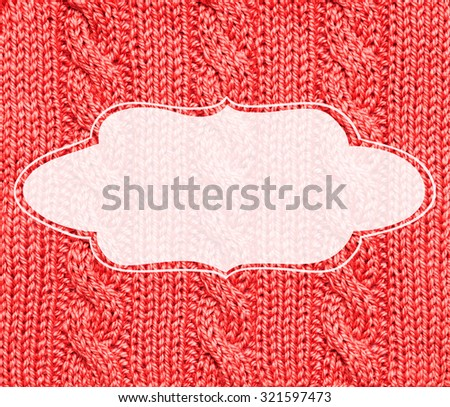 Woolen red knitted background with white blank vintage frame - winter theme. Winter Christmas holidays warm frame.
