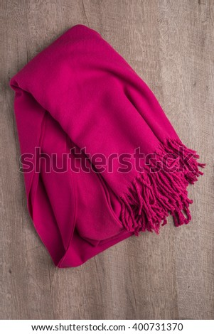 Woolen soft and worm scarf on rustic wooden background. Top view with copy space - stock photo