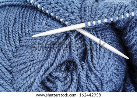 Woolen thread and knitting needle shown closeup - stock photo