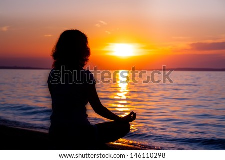Wooman at the beach meditating on sunrise - stock photo