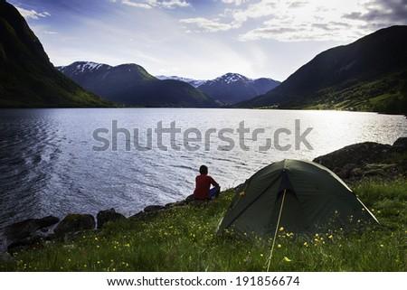woomen sitting  near lake in mountains, Norway - stock photo