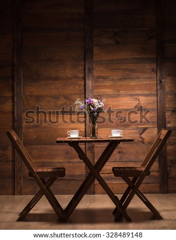 Woooden table and two chairs represented in cafe or restaurant for spending evening with a cup of coffee or tea. - stock photo