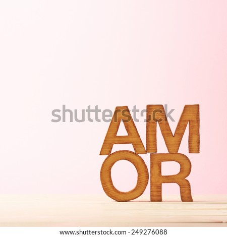 Word Amor meaning Love in multiple languages as a composition of wooden block letters against the pink background - stock photo