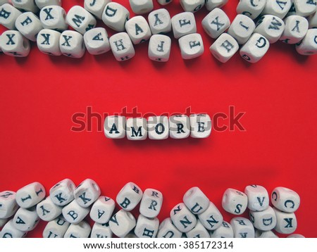 Word Amore meaning Love in Italian language as a composition of wooden block letters against the red background