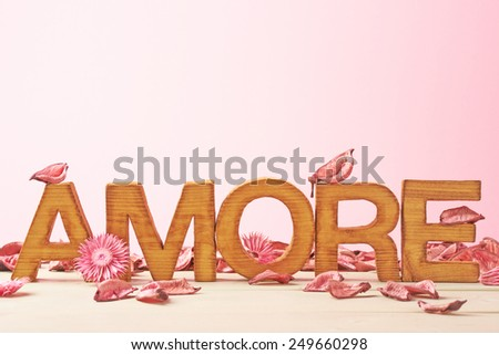 Word Amore meaning Love in Italian language as a composition of wooden block letters covered with the dried flower potpourri leaves against the pink background - stock photo