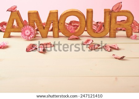 Word Amour meaning Love in French language as a composition of wooden block letters covered with the dried flower potpourri leaves against the pink background - stock photo
