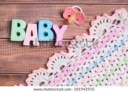 Word baby and nipple on a wooden background  - stock photo