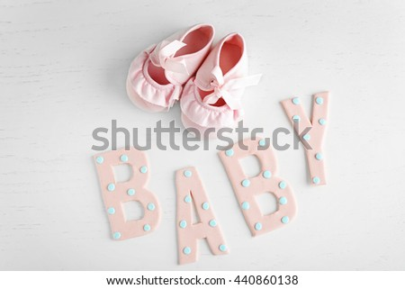 "Word ""Baby"" and shoes on white wooden background"