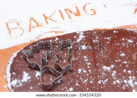 Word baking written in white flour, cookie cutters in shape of heart and christmas tree on dough for gingerbread, concept of baking and christmas time