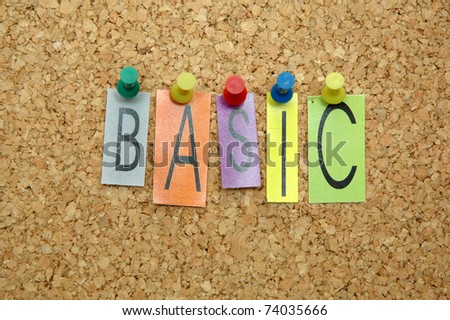 "Word "" Basic "" placed from colourful small letters on the cork board"