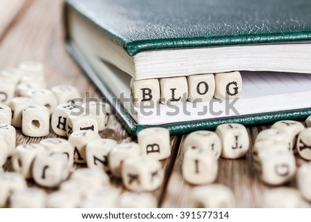 Word blog written on a wooden block in a book. On old wooden table.