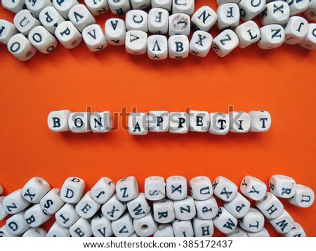 Word Bon Appetit of small white cubes next to a bunch of other letters on the surface of the composition on a orange background