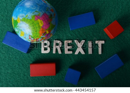 word BREXIT on green background with toy block and globe. Low light photography