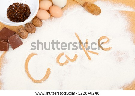 Word cake written in flour on table with ingredients.