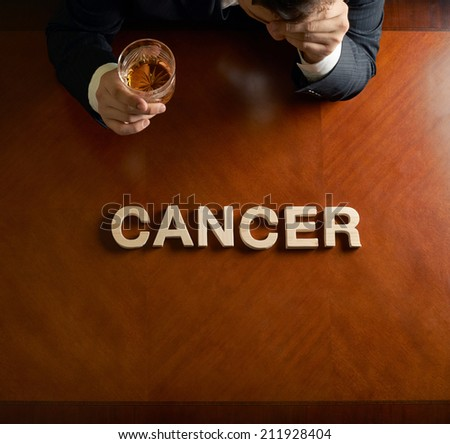 Word Cancer made of wooden block letters and devastated middle aged caucasian man in a black suit sitting at the table with the glass of whiskey, top view composition with dramatic lighting - stock photo