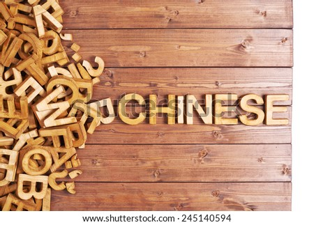 Word chinese made with block wooden letters next to a pile of other letters over the wooden board surface composition - stock photo