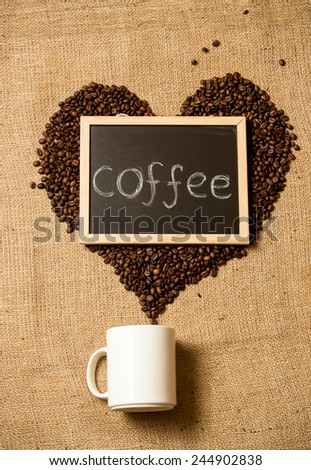 "Word ""coffee"" written on black chalkboard against heart of coffee beans  - stock photo"