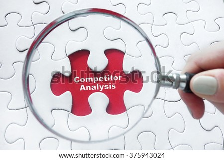 Word Competitor Analysis with hand holding magnifying glass over jigsaw puzzle - stock photo