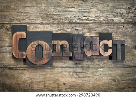 """word """"contact"""" written with vintage letterpress printing blocks on rustic wood background - stock photo"""