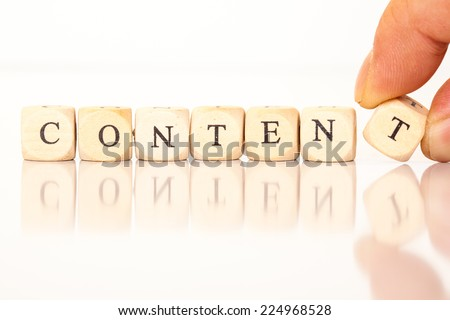 Word Content spelled from single dice letters, with reflection on bottom, hand putting on the last letter. - stock photo