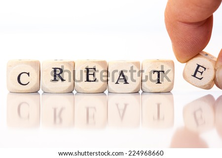 Word Create spelled from single dice letters, with reflection on bottom, hand putting on the last letter. - stock photo