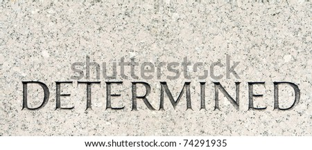 "Word ""Determined"" Carved in Gray Granite Stone"