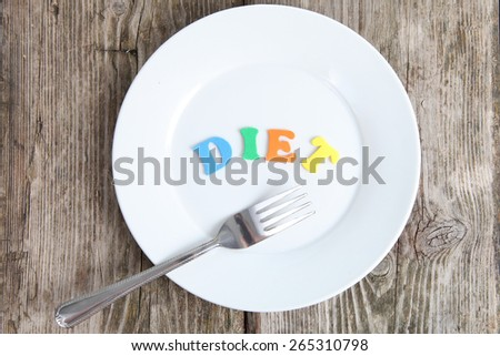 "Word ""diet"" and fork on a white plate on a wooden table - stock photo"