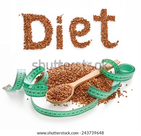 Word Diet composed of premium buckwheat groats on white background with wooden spoon and measuring tape  - stock photo