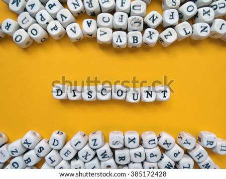 Word Discount of small white cubes next to a bunch of other letters on the surface of the composition on a yellow background
