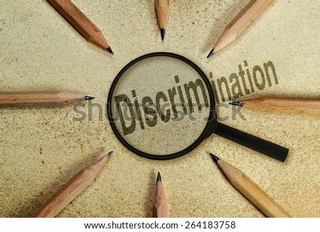 Word Discrimination under a magnifier as a conceptual image about the phenomena - stock photo