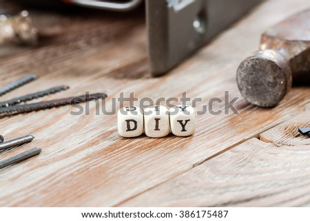 Word DIY written on a wooden block. Work tools concept.