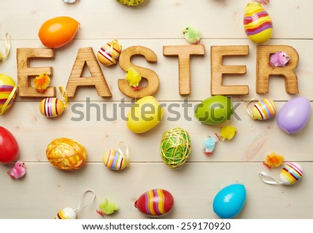 Word Easter made of wooden letters and surrounded with multiple egg decorations as a festive Easter background composition - stock photo