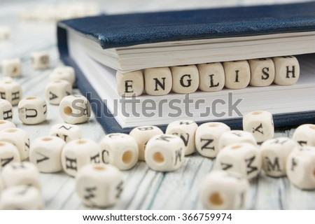 Word english made with block wood letters next to a pile of other letter over  wooden table - stock photo