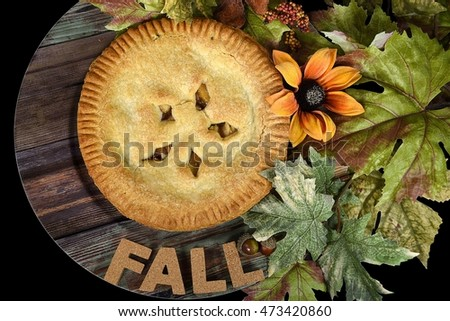 word fall in cork letters with apple pie on wood plate and leaves