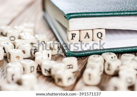 Word FAQ written on a wooden block in a book. On old wooden table.