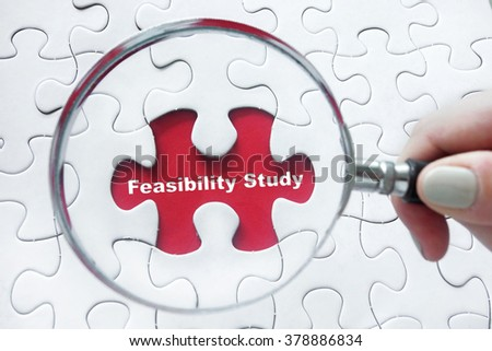 Word Feasibility Study with hand holding magnifying glass over jigsaw puzzle