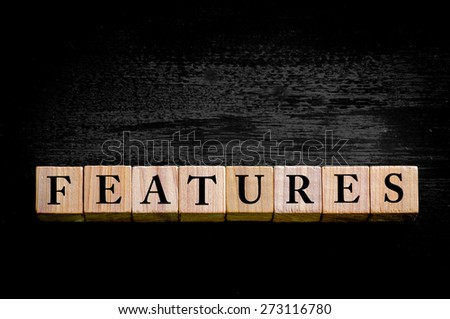 Word FEATURES. Wooden small cubes with letters isolated on black background with copy space available. Concept image.