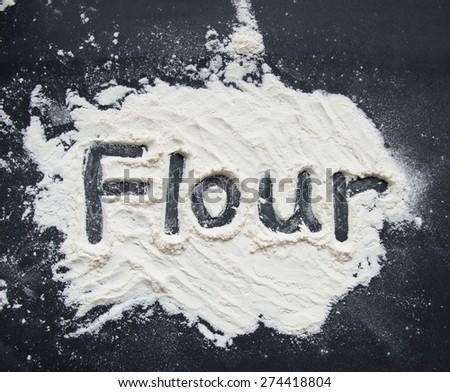 Word Flour Written on Flour on Black Background - stock photo