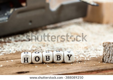 Word HOBBY written on a wooden block. Work tools concept.